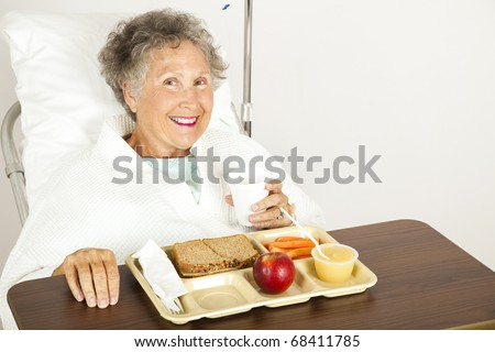 Senior hospital patient eating her lunch on a tray. - stock photo