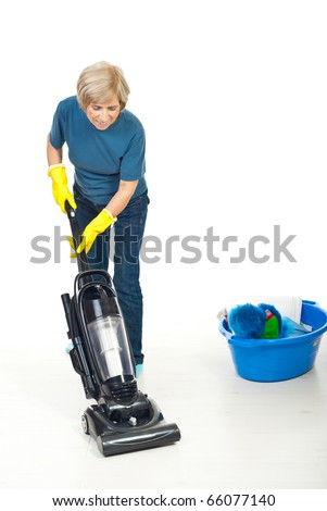 Senior housewife using vacuum cleaner to cleaning wooden floor - stock photo