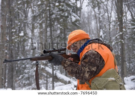 Senior hunter aiming a deer in his sight under the snow,Quebec, Canada - stock photo