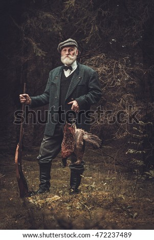 Senior hunter with a shotgun and pheasants in a traditional shooting clothing on a dark forest background.