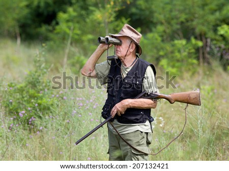 Senior hunter with shotgun looking through binoculars in forest - stock photo