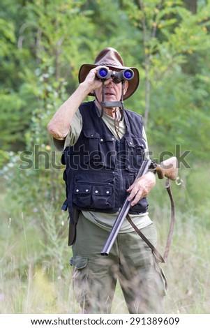 Senior hunter with shotgun looking through binoculars in forest - stock photo