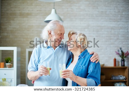 Senior husband and wife holding glasses with healthy homemade fruit drink and looking at one another - stock photo