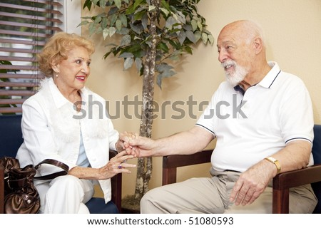 Senior husband and wife wait together and holding hands in the doctors waiting room. - stock photo