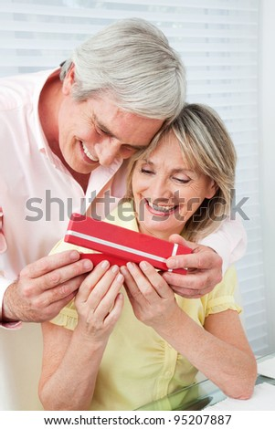 Senior husband offering his happy wife a gift - stock photo