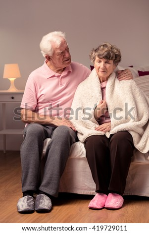 Senior husband taking care of his wife, cozy home interior - stock photo