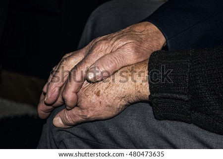 Senior husband touching the hand of his old wife.