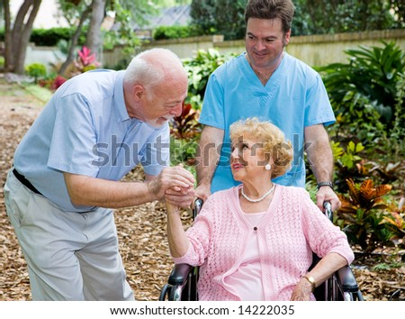 Senior husband visiting his disabled wife on the grounds of the nursing home while a nurse pushes her wheelchair. - stock photo