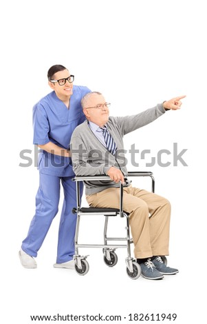 Senior in a wheelchair showing something to doctor isolated on white background - stock photo