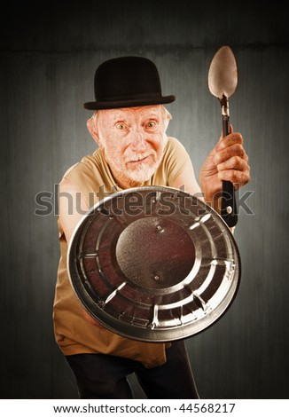 Senior in bowler hat defending himself with spoon and can lid - stock photo