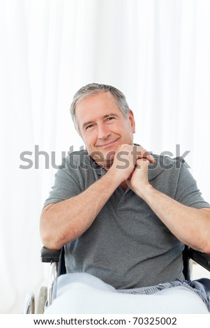 Senior in his wheelchair looking at the camera at home - stock photo