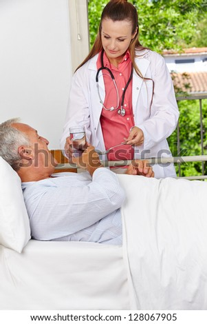 Senior in hospital taking medicine with a glass of water - stock photo