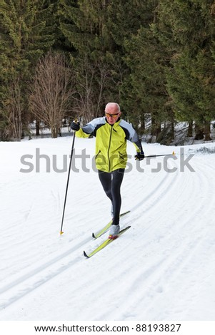 senior in winter on snow to cross country skiing with skis - stock photo