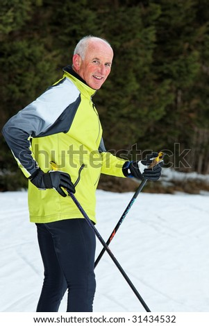 Senior in winter on snow with skis at the Cross - stock photo