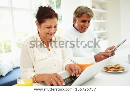 Senior Indian Couple Using Laptop And Digital Tablet At Home - stock photo