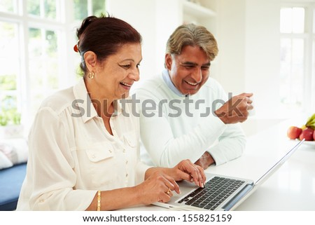 Senior Indian Couple Using Laptop At Home - stock photo
