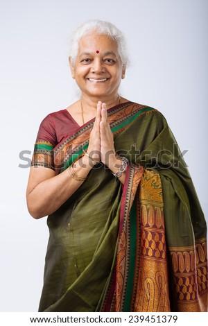 Senior Indian woman in namaste pose - stock photo