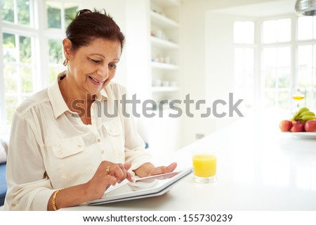 Senior Indian Woman Using Digital Tablet At Home