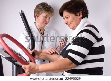 Senior is being observed by doctor after training, measuring blood pressure - stock photo