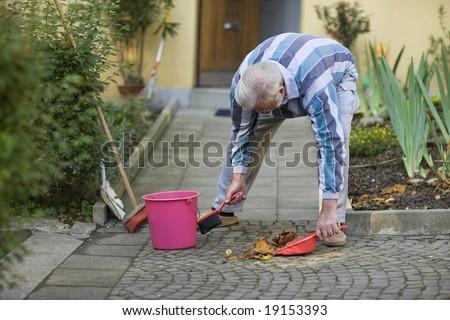 Senior is sweeping his sidewalk in autumn - stock photo