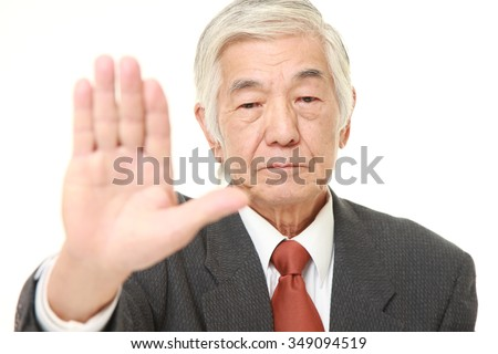 senior Japanese businessman making stop gesture