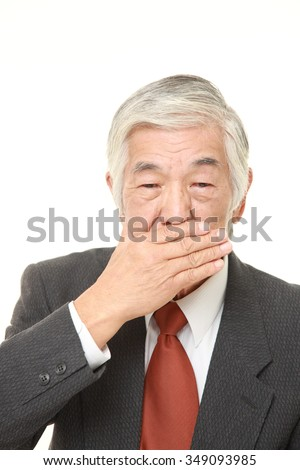 senior Japanese businessman making the speak no evil gesture