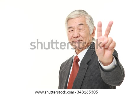 senior Japanese businessman showing a victory sign