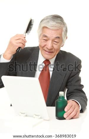 senior Japanese businessman using hair restorer - stock photo