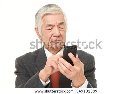 senior Japanese businessman using smart phone looking confused - stock photo