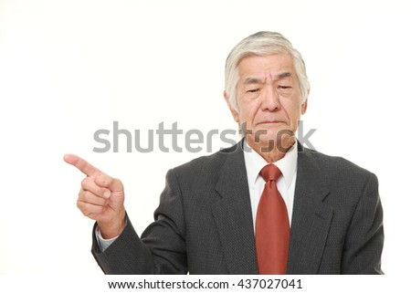 senior Japanese businessman wearing a gray suit doubting