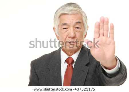 senior Japanese businessman wearing a gray suit making stop gesture