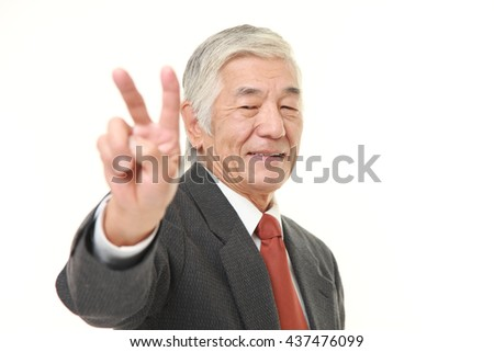 senior Japanese businessman wearing a gray suit showing a victory sign