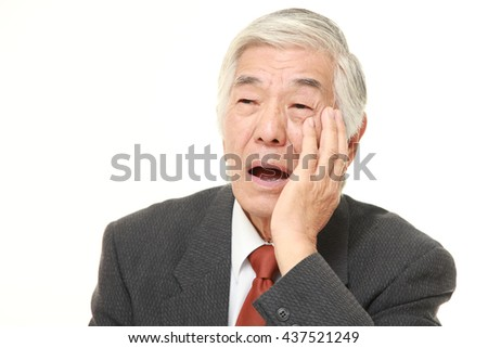 senior Japanese businessman wearing a gray suit suffers from toothache