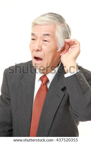 senior Japanese businessman wearing a gray suit with hand behind ear listening closely - stock photo
