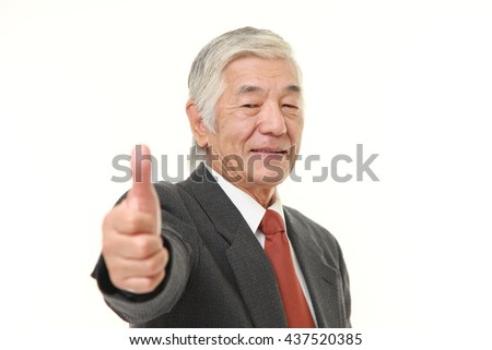 senior Japanese businessman wearing a gray suit with thumbs up gesture