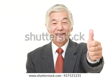 senior Japanese businessman wearing a gray suit with thumbs up gesture - stock photo