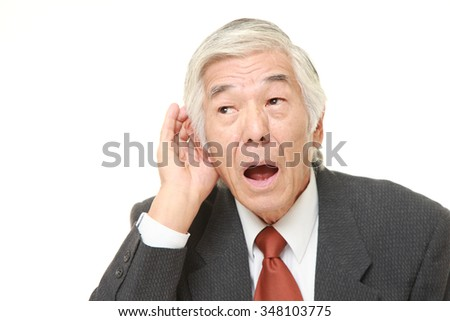 senior Japanese businessman with hand behind ear listening closely - stock photo