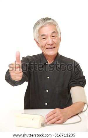senior Japanese man checking his blood pressure - stock photo