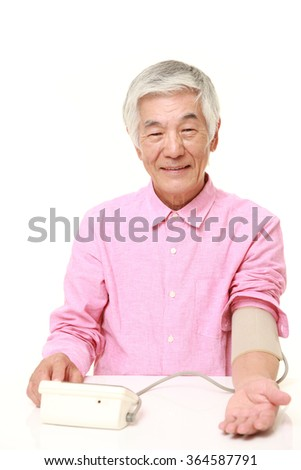 senior Japanese man checking his blood pressure