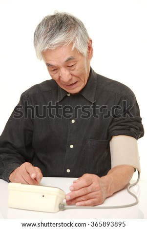senior Japanese man checking his blood pressure shocked