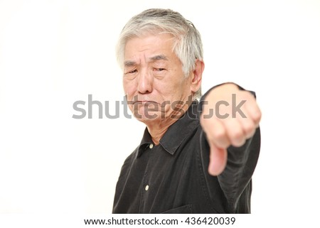 senior Japanese man in a black shirts with thumbs down gesture