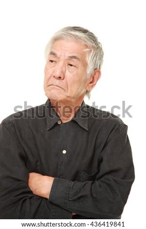 senior Japanese man in a black shirts worries about something - stock photo