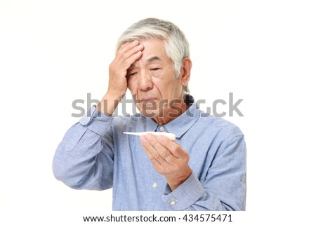 senior Japanese man in a blue shirts with fever - stock photo