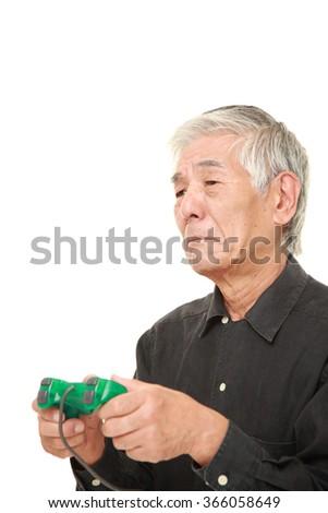 senior Japanese man losing playing video game - stock photo