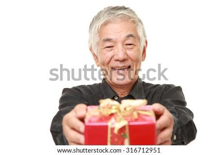 senior Japanese man offering a gift - stock photo