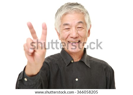 senior Japanese man showing a victory sign - stock photo