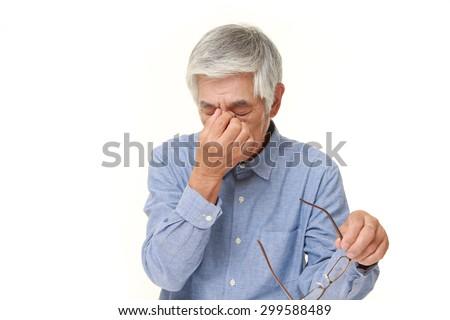 senior Japanese man suffers from Asthenopia - stock photo
