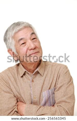 senior Japanese man thinks about something - stock photo