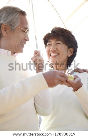 Senior Japanese man to pass a present to his wife
