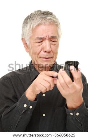 senior Japanese man using smart phone looking confused - stock photo